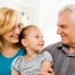 Grandparents with little girl sitting at home and enjoying