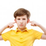 a teenage boy plugs ears